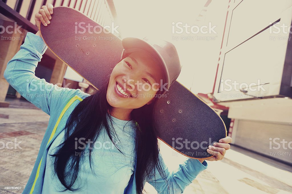 young woman skateboarder on street stock photo