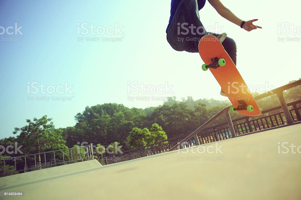 young woman skateboarder skateboarding at skatepark stock photo
