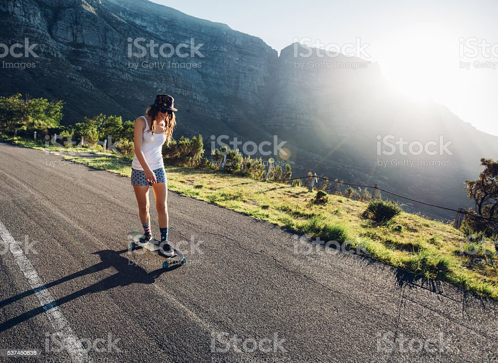 Young woman skating outdoors on rural road stock photo