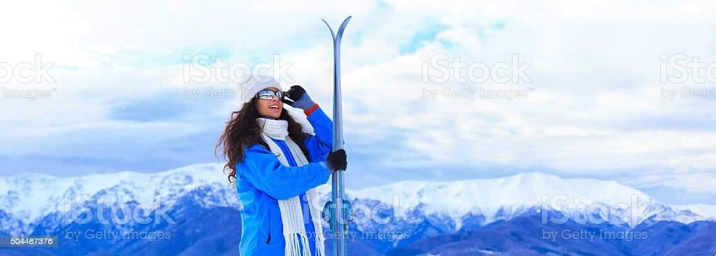 Young woman skiing in the winter mountain - panoramic view stock photo