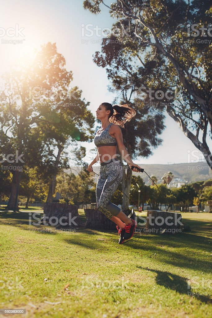Young woman skipping with a jump rope stock photo