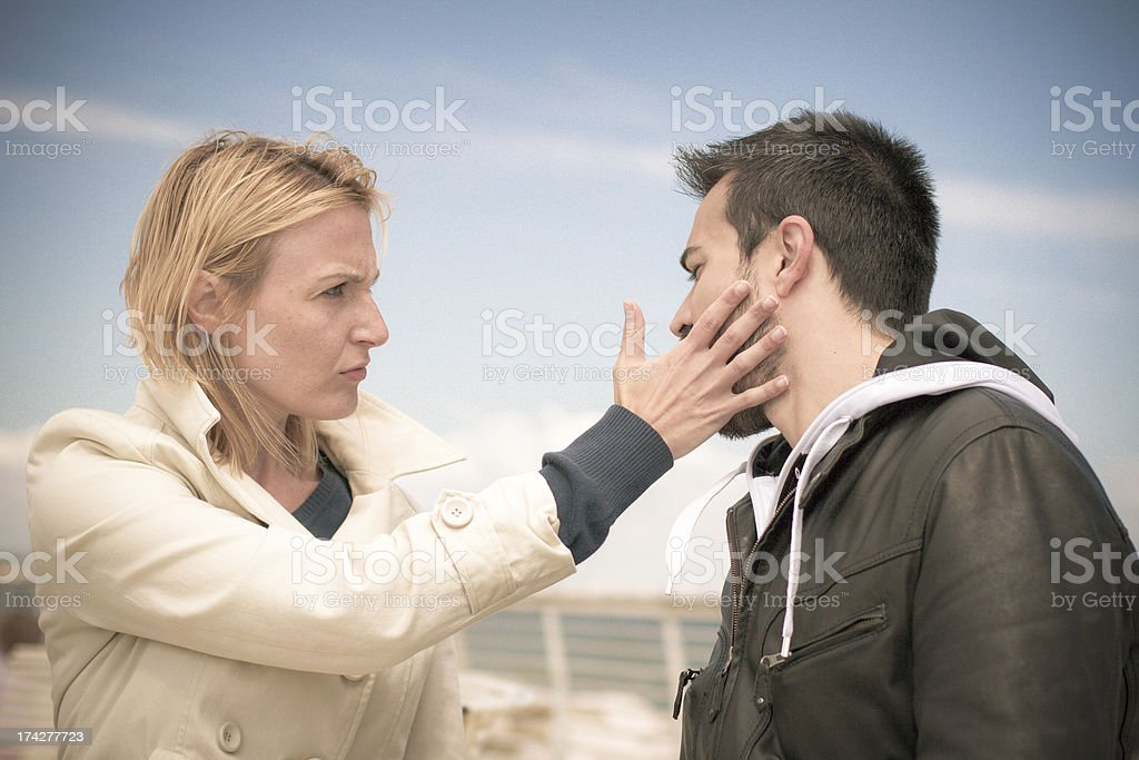 young woman slapping man at wharf stock photo