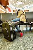 Young woman sleeping an airport terminal seat