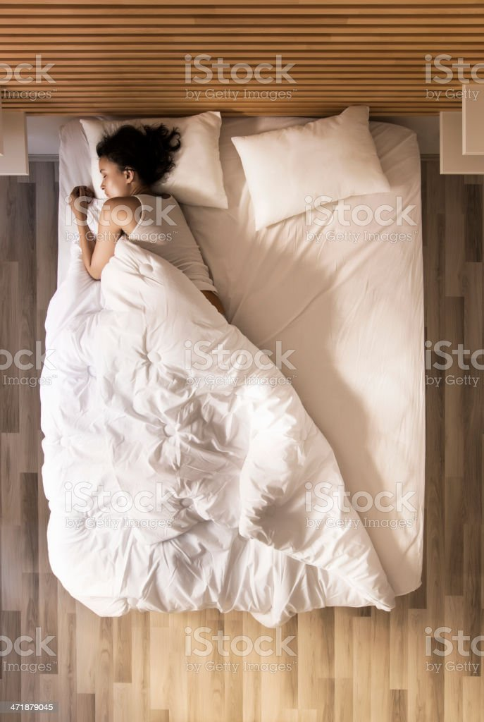 young woman sleeping in bed stock photo