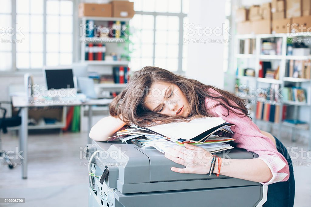 Young woman sleeping in office stock photo