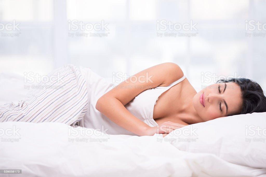 Young woman sleeping in striped pyjamas stock photo
