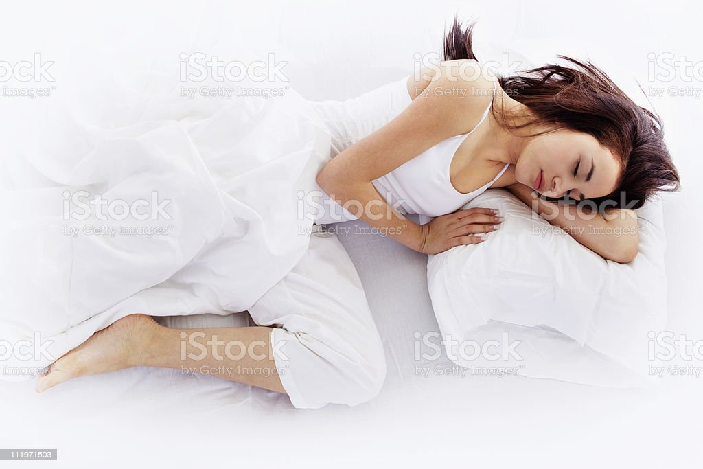 Young woman sleeping on white bed stock photo