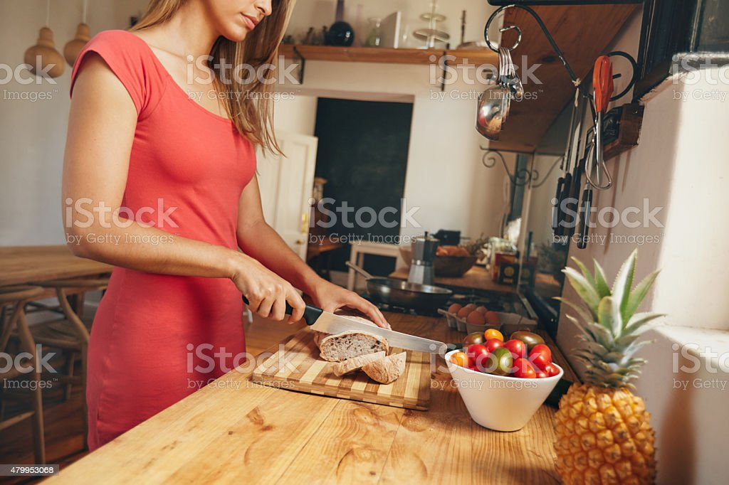 Young woman slicing a loaf of bread in kitchen stock photo