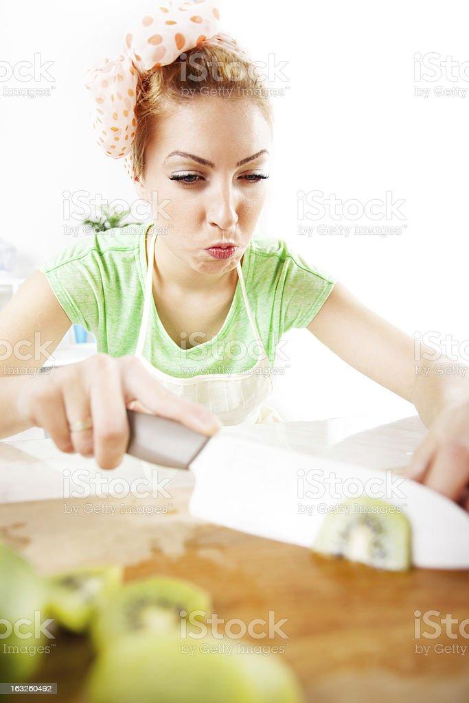 Young woman slicing kiwi. royalty-free stock photo