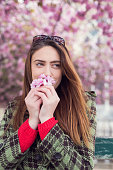 Young woman smelling cherry blossom