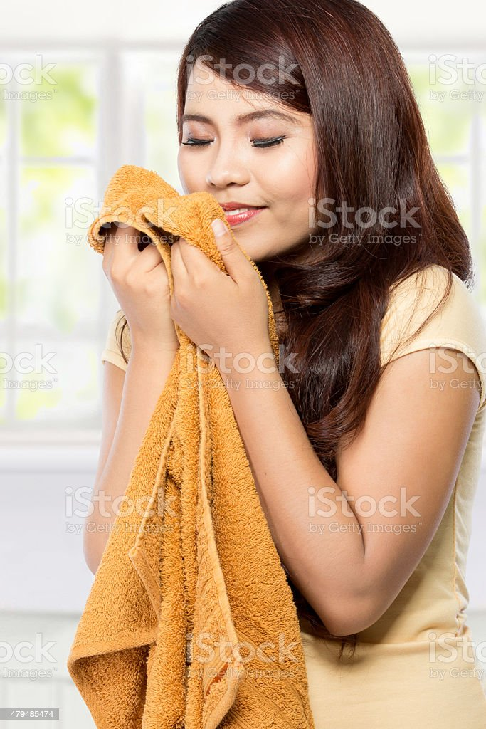 young woman smelling clean fresh laundry stock photo