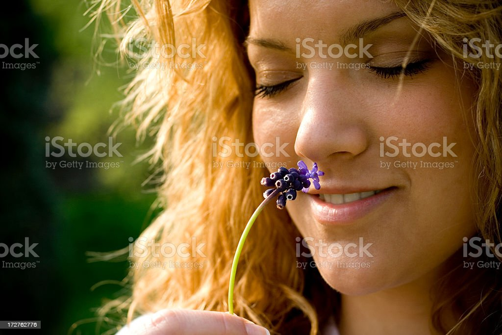 Young woman smelling flower, green background royalty-free stock photo
