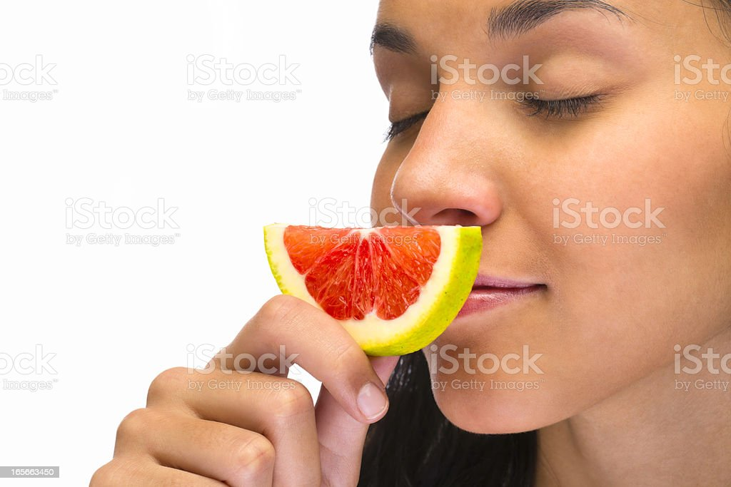 young woman smelling grapefruit slice royalty-free stock photo
