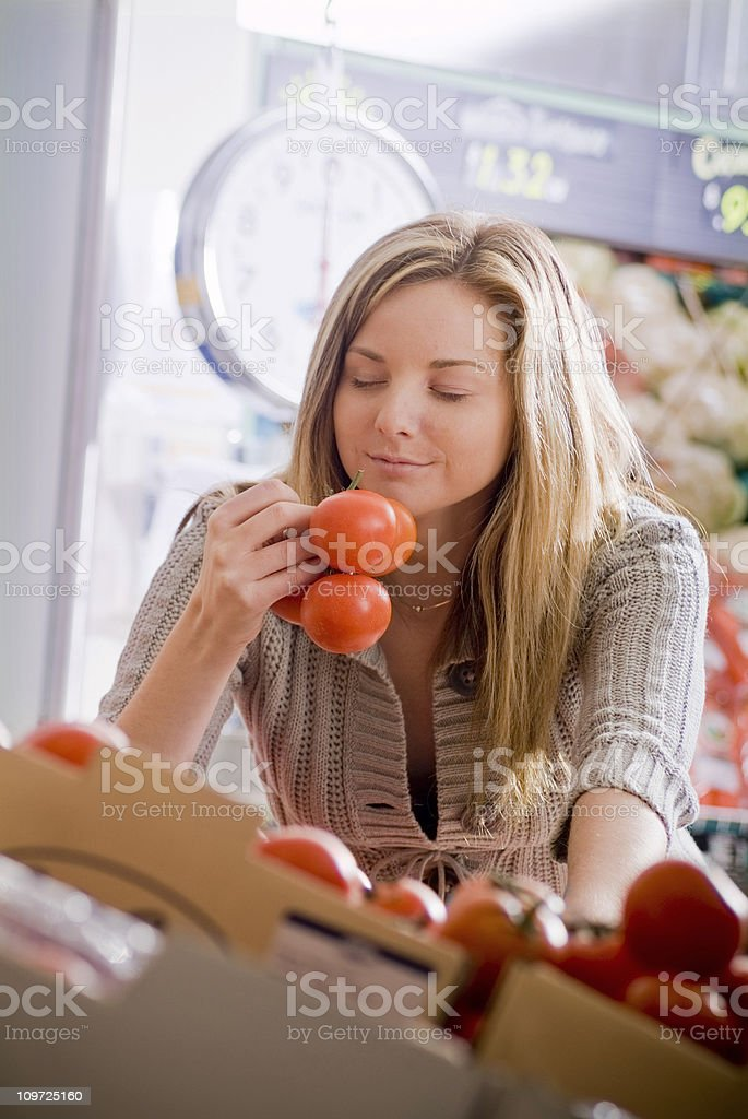 Young Woman Smelling Tomatoes at the Market royalty-free stock photo