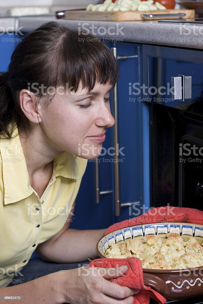 Young woman smells just baked cauliflower stock photo