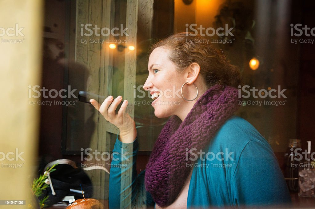 Young woman smiles as she talks on speaker phone stock photo