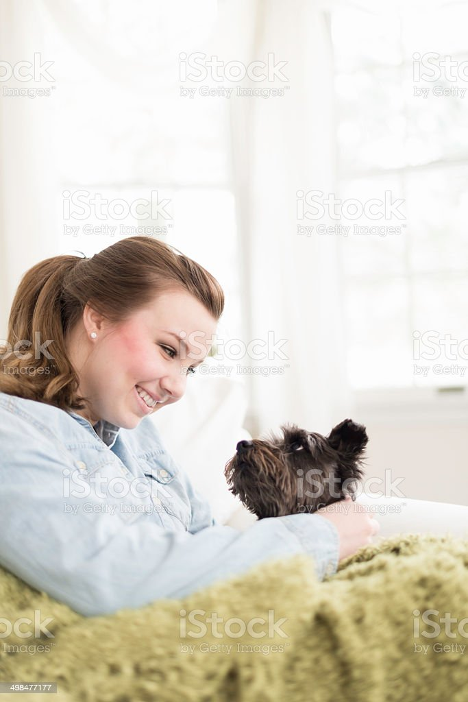 Young Woman Smiles at Her Dog stock photo