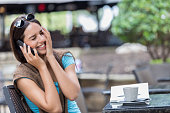 Young woman smiles while using smart phone at coffee shop