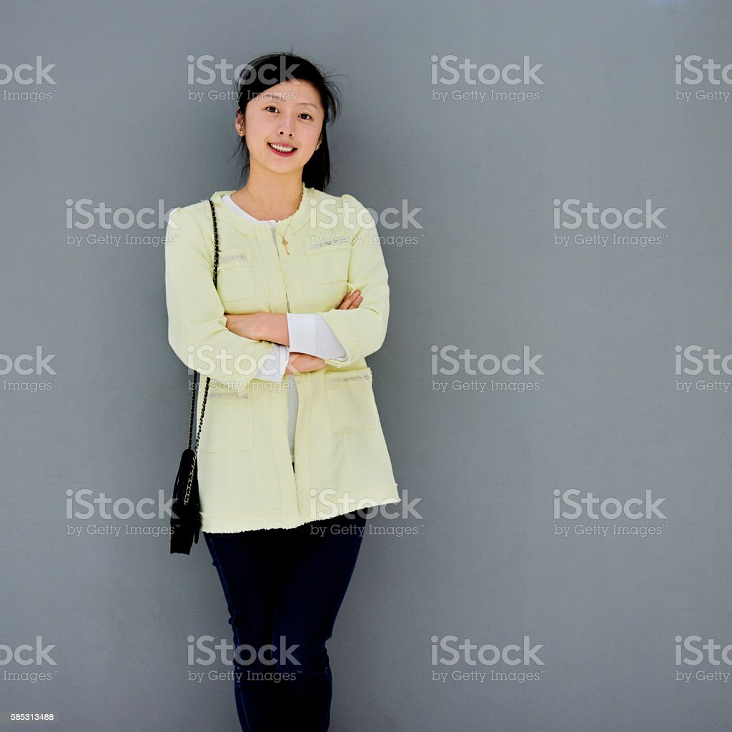 Young woman smiling against gray wall stock photo
