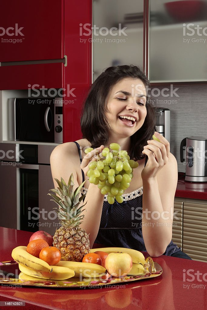 Young woman smiling and holding a bunch of grapes royalty-free stock photo