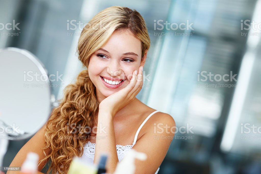 Young woman smiling and loving the way her skin feels stock photo