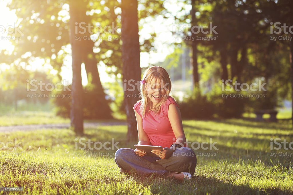 Young woman smiling and reading tablet on vacation royalty-free stock photo