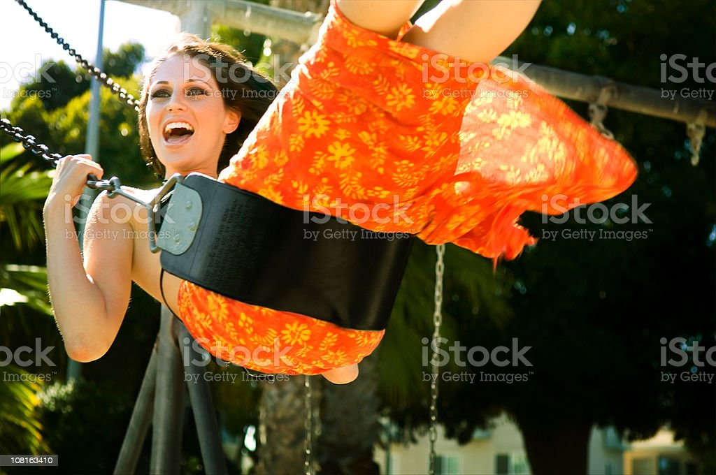 Young Woman Smiling and Swinging on Playground Swing royalty-free stock photo