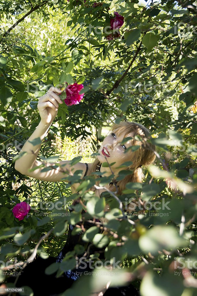 Young woman smiling as she reaches for rose. royalty-free stock photo