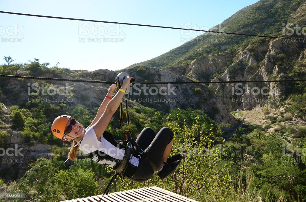 Young woman smiling as she zip lines over a valley stock photo