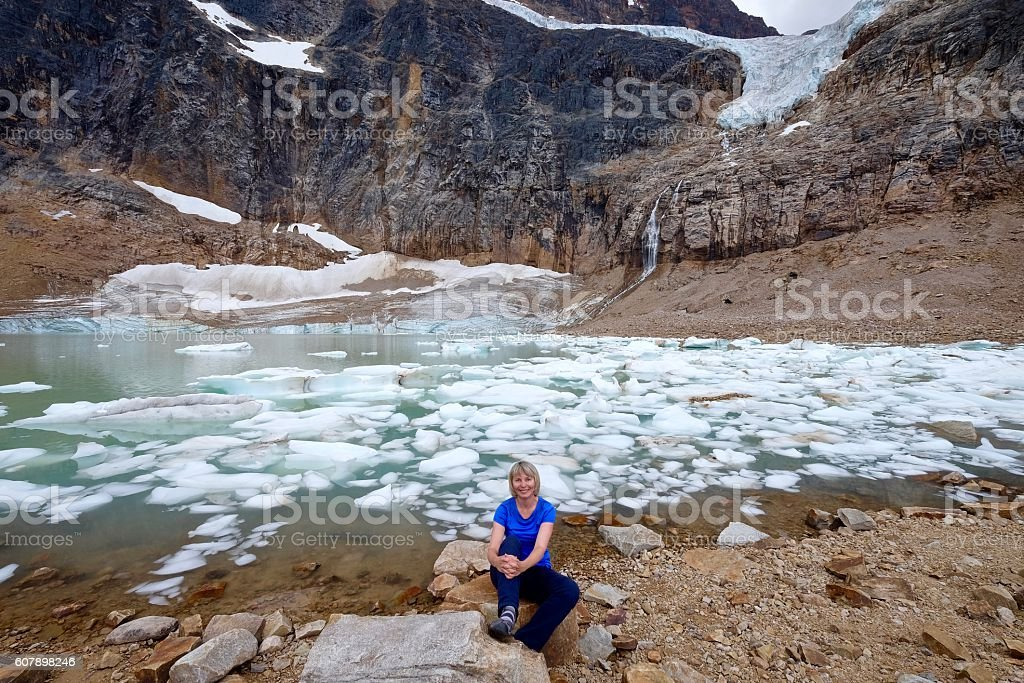Young woman smiling by alpine lake with icebergs under glacier. stock photo