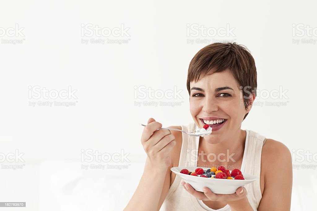 Young Woman Smiling Eating Bowl of Fruit royalty-free stock photo