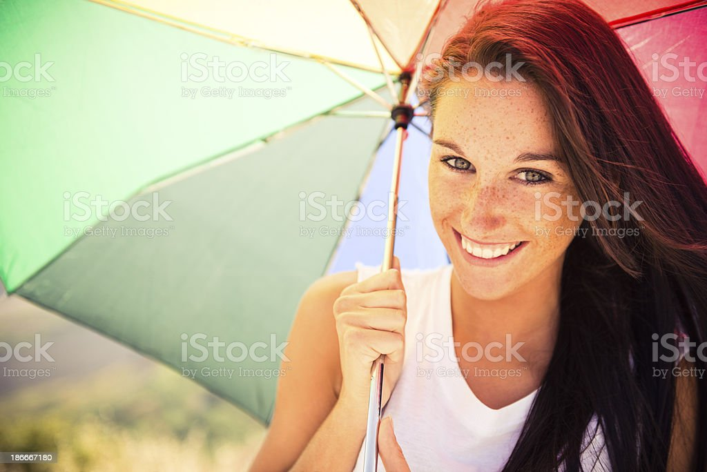 Young woman smiling holding an umbrella royalty-free stock photo
