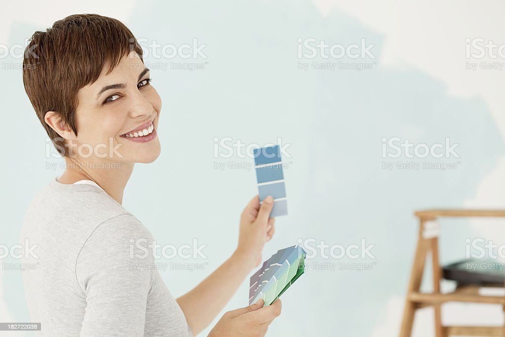 Young Woman Smiling Holding Paint Samples royalty-free stock photo