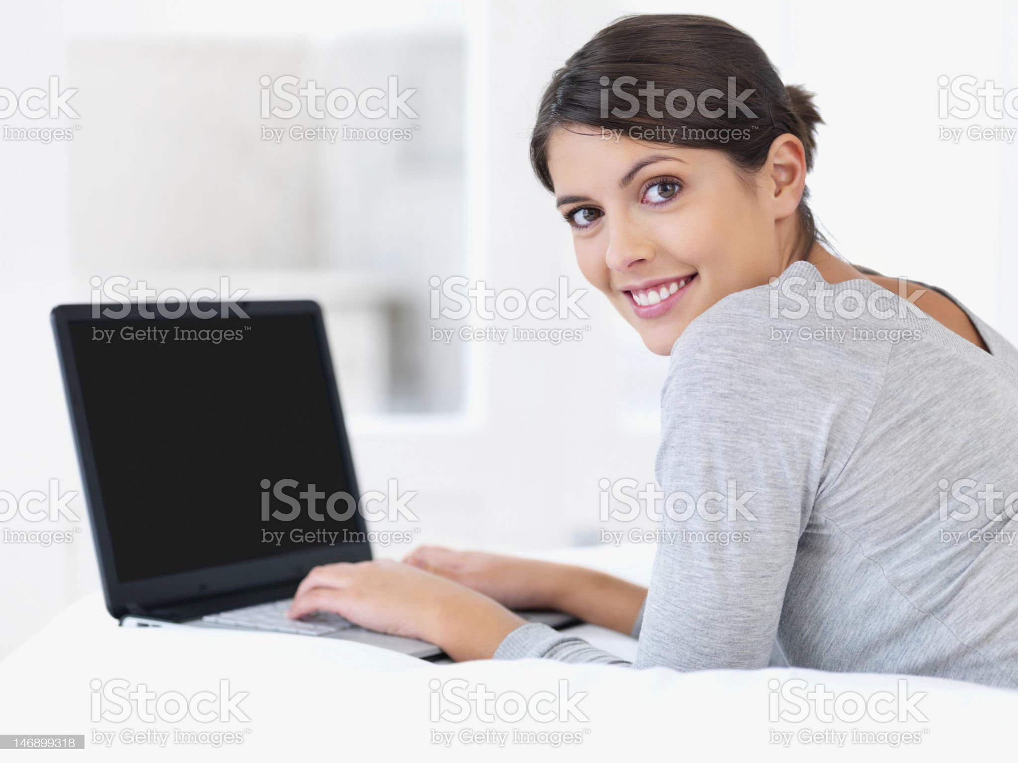 Young woman smiling in bed with a laptop royalty-free stock photo