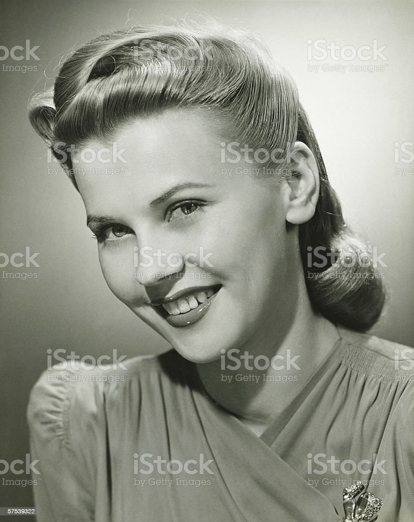 Young woman smiling in studio, (B&W), portrait stock photo