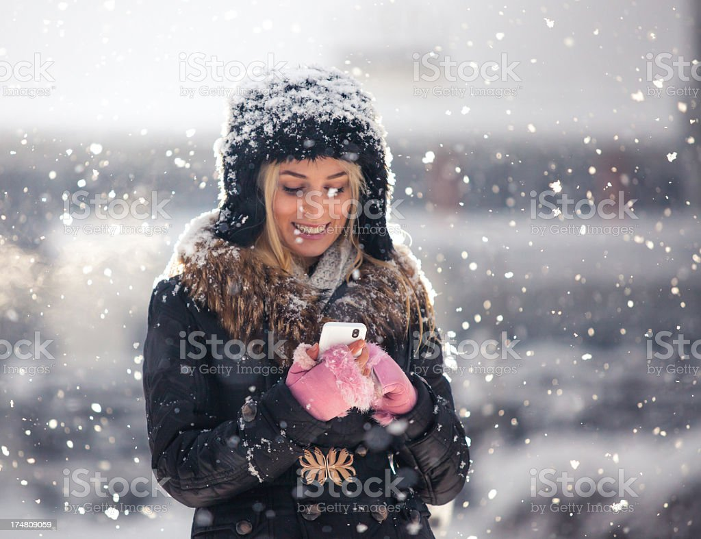 Young woman smiling looking down at phone in a snowy day royalty-free stock photo