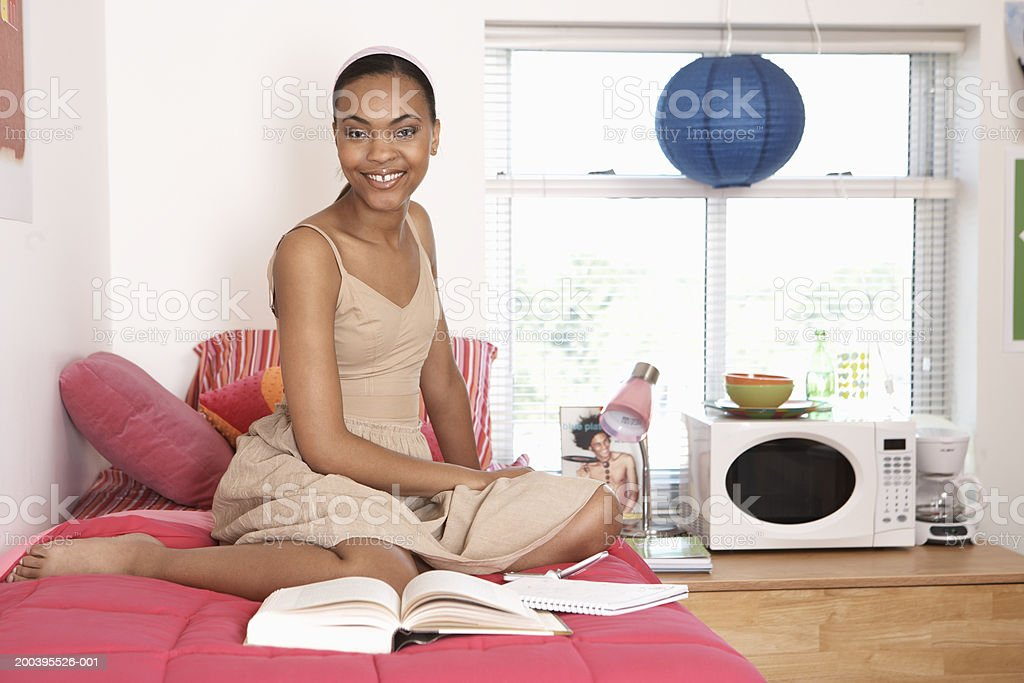 Young woman smiling on bed in dorm room, portrait stock photo