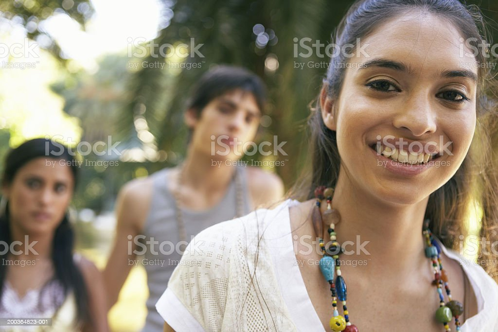 Young woman smiling, portrait, teenage couple (16-18) in background royalty-free stock photo