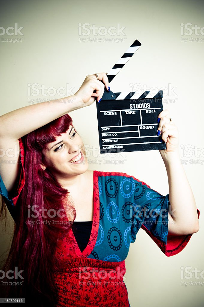 Young woman smiling showing movie clapper board stock photo