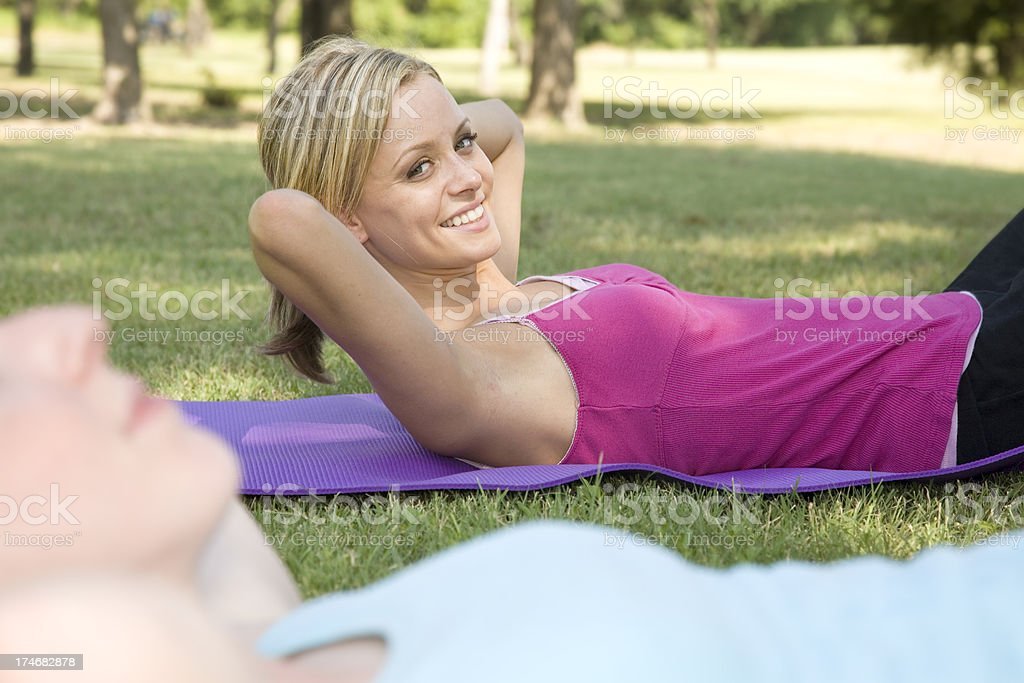 Young Woman Smiling While Doing Sit-ups with Her Class royalty-free stock photo