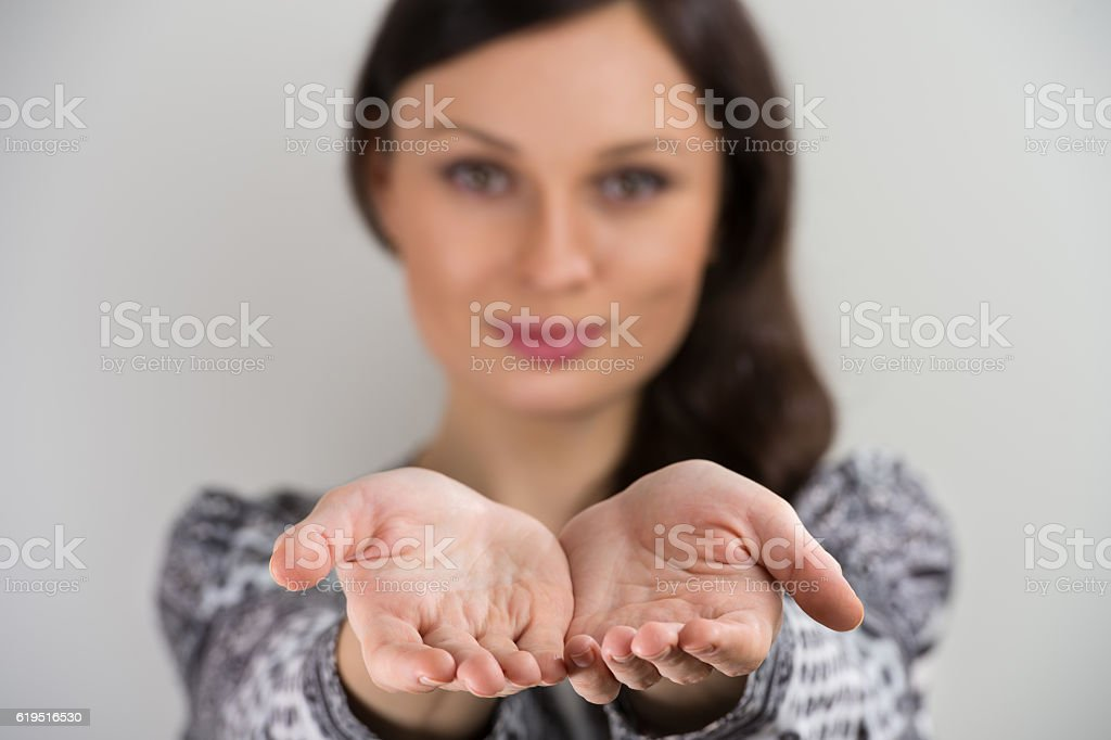 Young woman smiling with hands cupped together stock photo