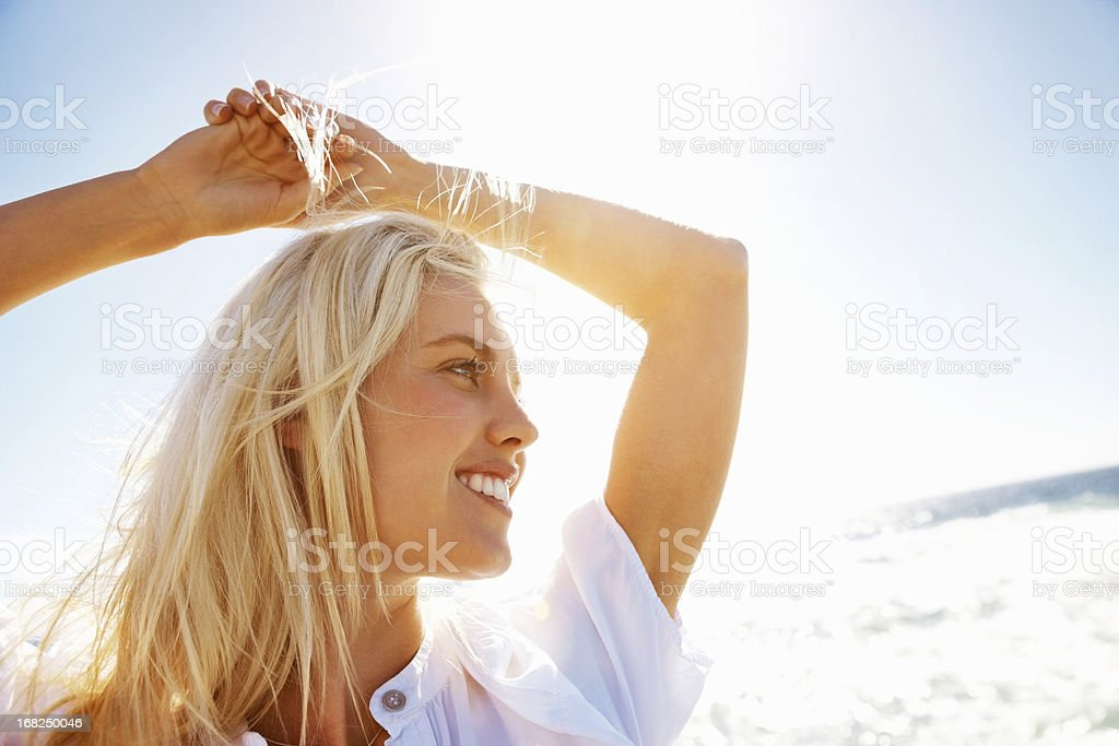 Young woman smiling with hands over head on beach stock photo