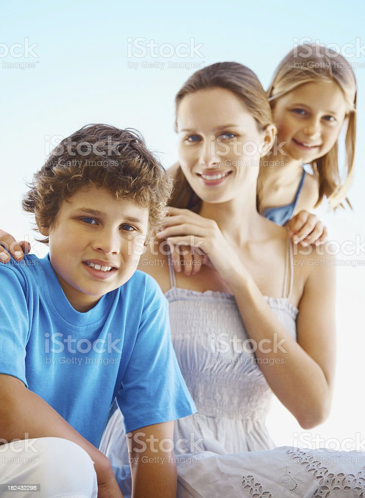 Young woman smiling with her children against clear sky royalty-free stock photo