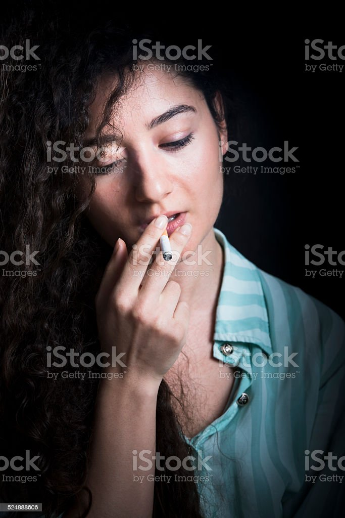 Young woman smokes a cigarette stock photo
