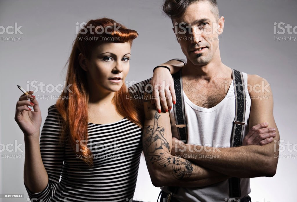 Young Woman Smoking and Leaning on Man with Tattoos stock photo