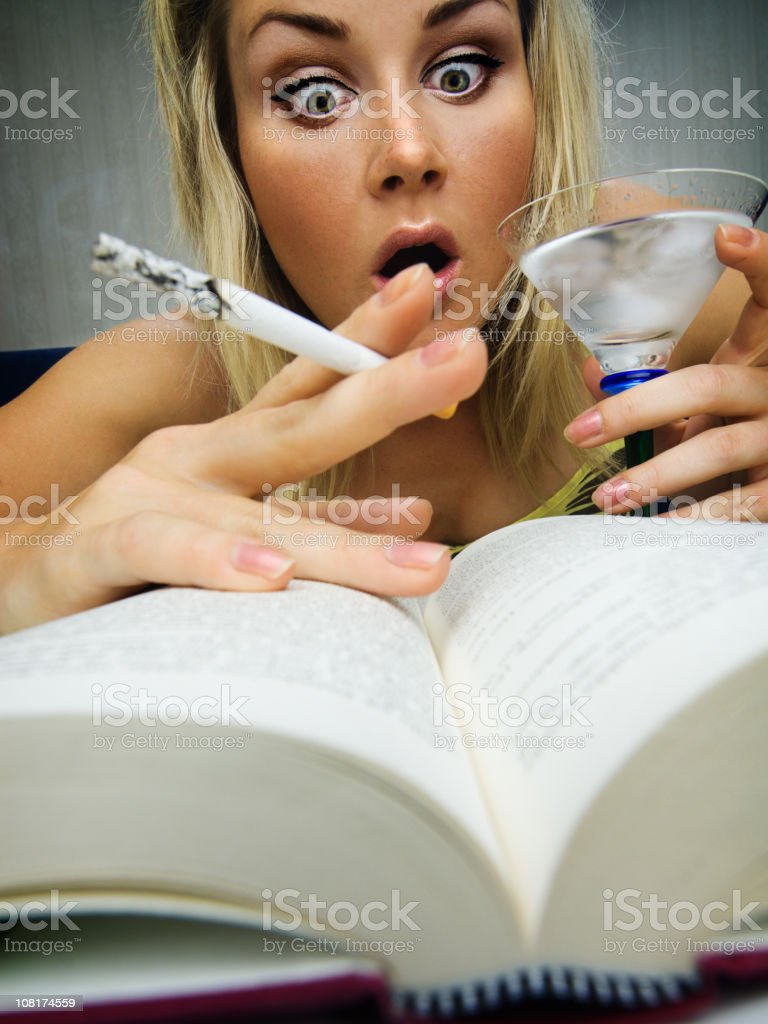Young Woman Smoking Cigarette and Reading stock photo