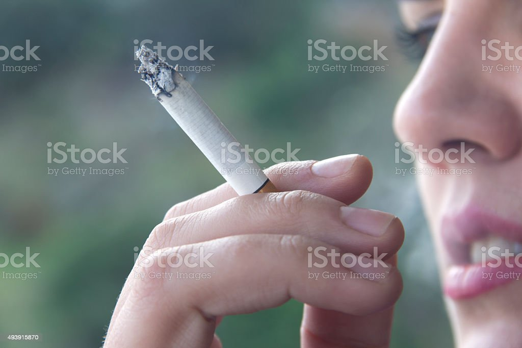 young woman smoking cigarette stock photo
