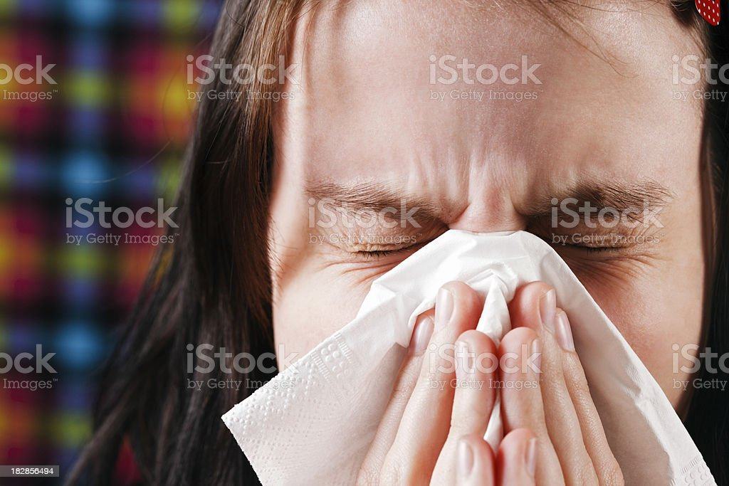 Young woman sneezes into tissue - flu season coming! royalty-free stock photo