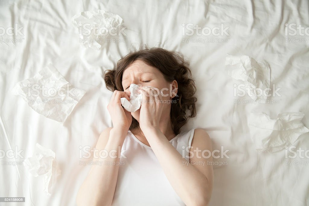 Young woman sneezing into tissue stock photo