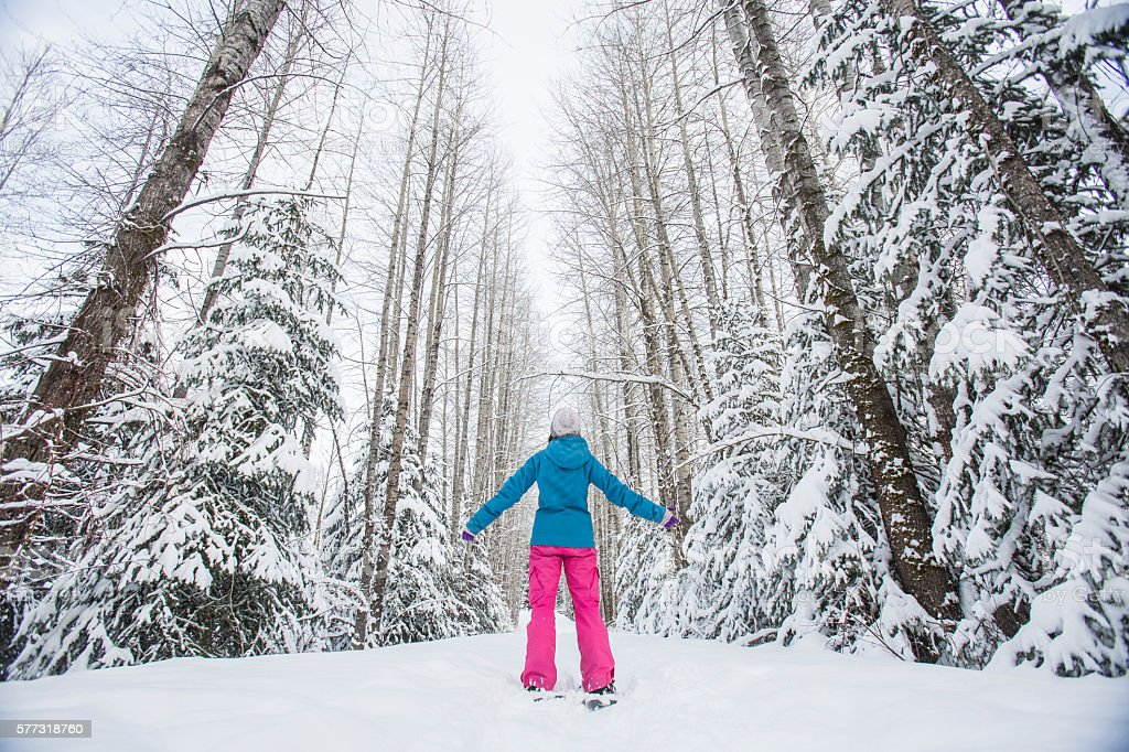 Young woman snowshoeing. stock photo